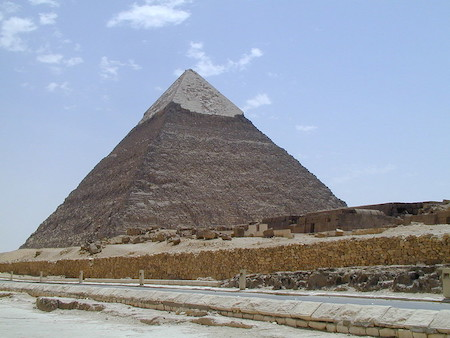 A long pyramid can be seen against a blue sky backdrop with a few small clouds.