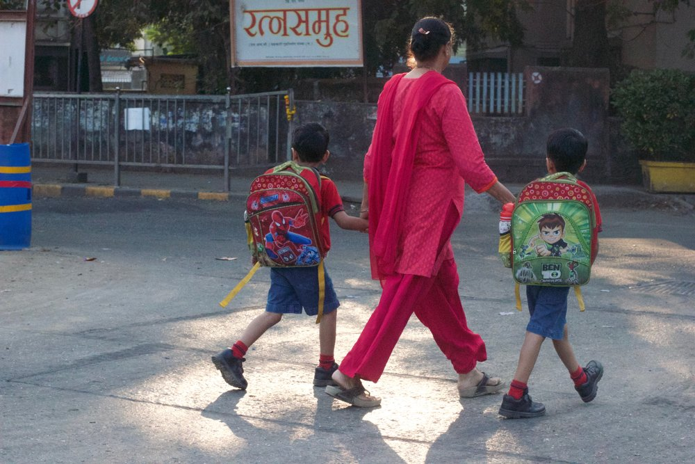 woman crossing the street holding hands with two boys