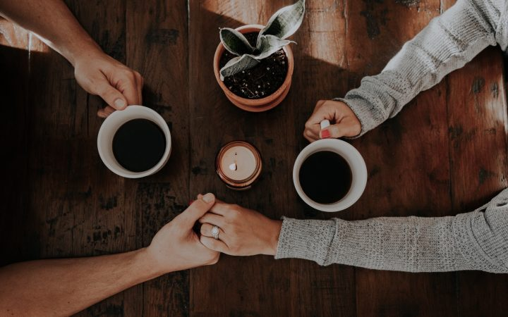 A married couple holding hands while holding coffee.