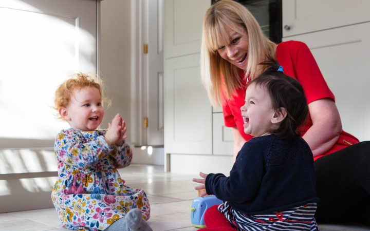 An image of a nanny with her client's kids, playing gleefully