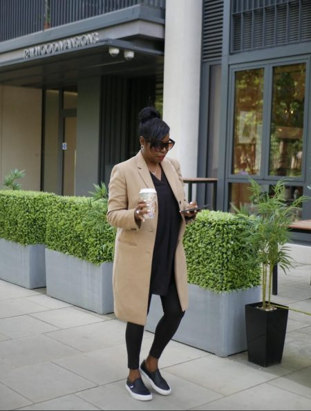 Tracy Reid, snapshot of her on the go with a coffee in her hand and on her phone.