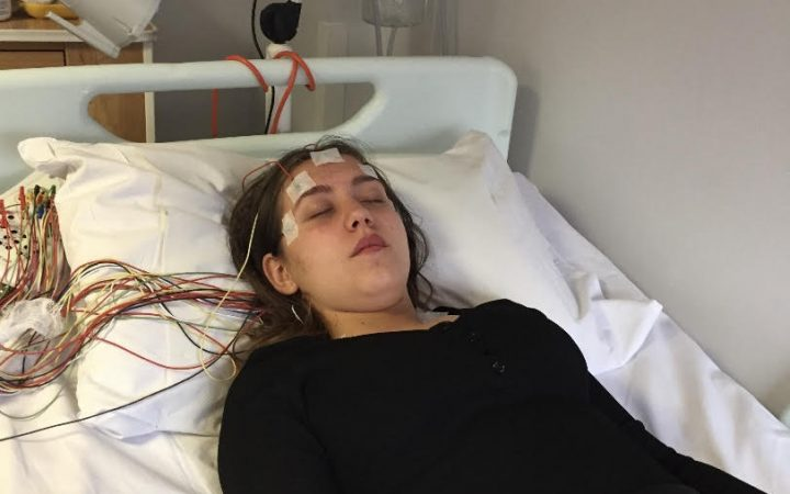 Fiona Likurti, going for a regular hospital check up, connected to a machine with wires on her forehead.