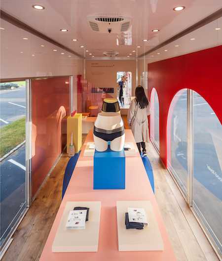 The interior of Visibility's Period Management System mobile concept store, designed for THINX. Period-absorbing underwear is displayed on a central storage platform, accented with a warm colour palette of reds and pinks.