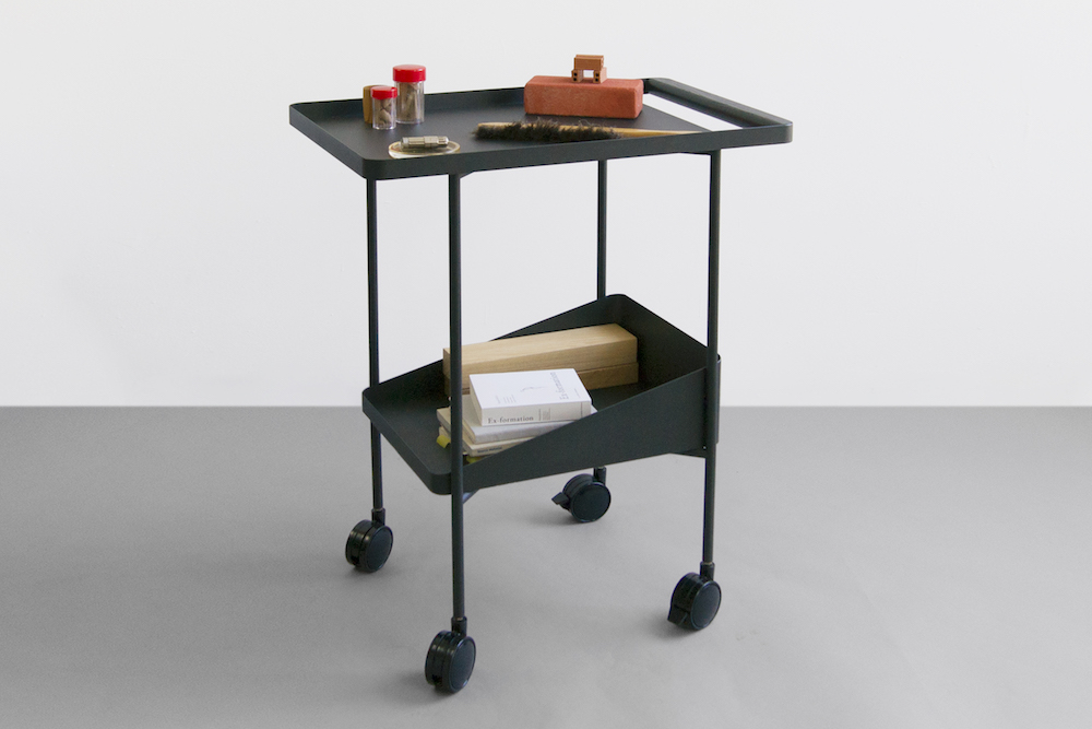 Visibility's 'Barbican Trolley', a service trolley built from ash wood and steel that takes on architectural qualities. Pictured is a selection of books and tools held within the two trays.