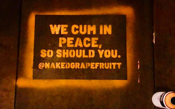 "Naked Grapefruits slogan: ""We cum in peace. So should you."" stencilled on the pavement."