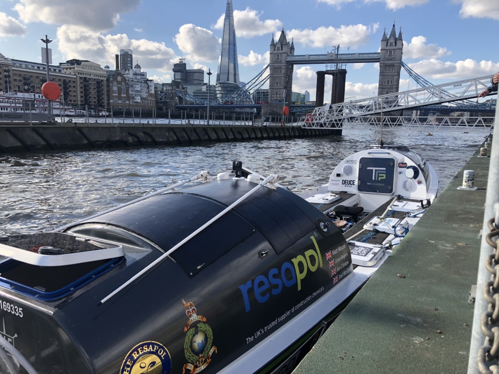The Ocean Revival 2020 ocean rowing boat docked at HMS President in London. Tower Bridge and The Shard can be seen in the background.