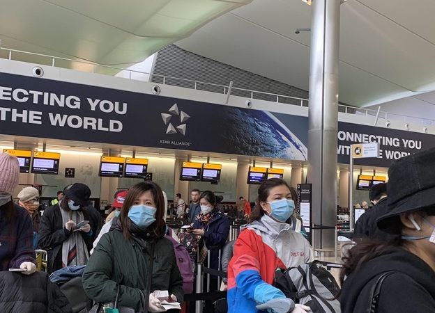 People in masks at Heathrow Airport