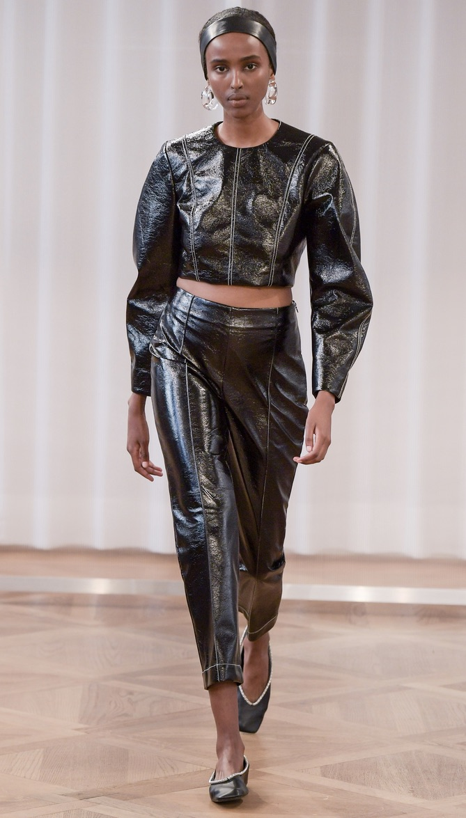 A photograph of a black model, wearing a black leather two piece outfit consisting of a long sleeved crop top and cropped trousers, for Baum und Pferdgarten's SS21 show