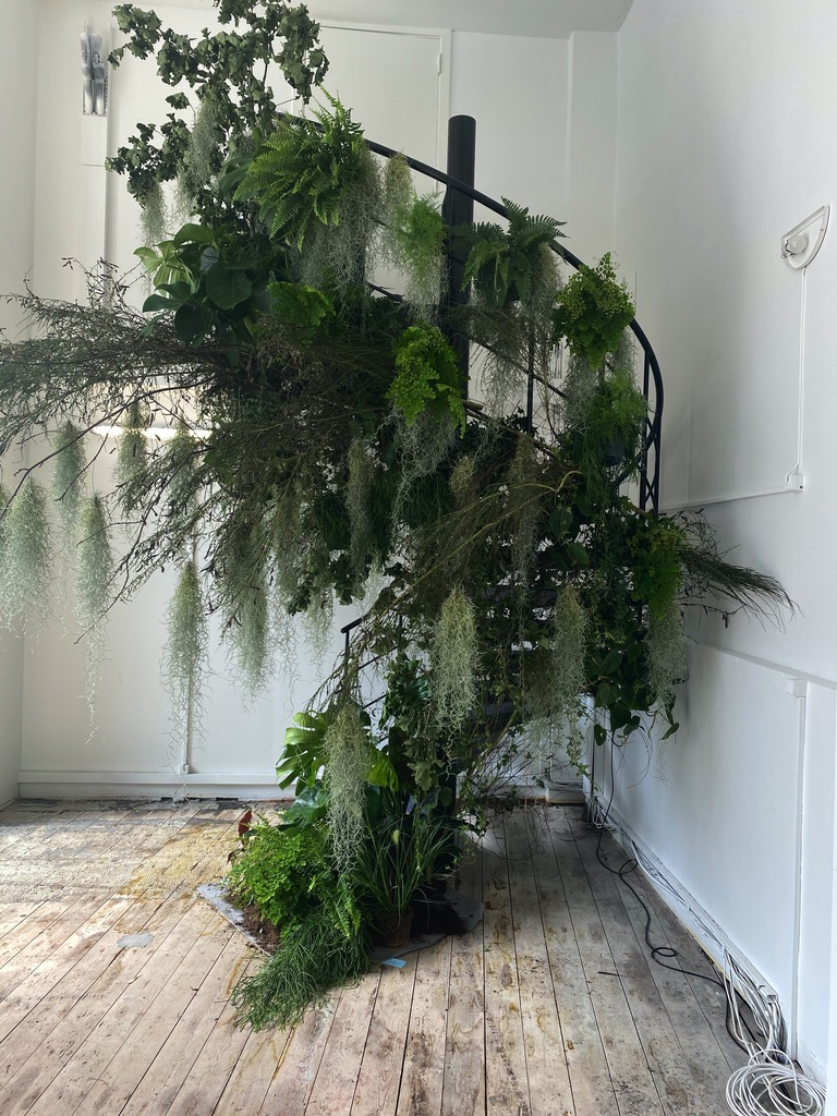 A metal stairway adorned with lush greenery for the Rains SS21 Presentation in Copenhagen