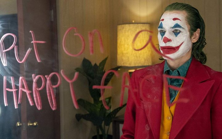 "A scene from The Joker. Joker stands in front of a mirror, with the words ""put on a happy face written on it. Joker isn't smiling"