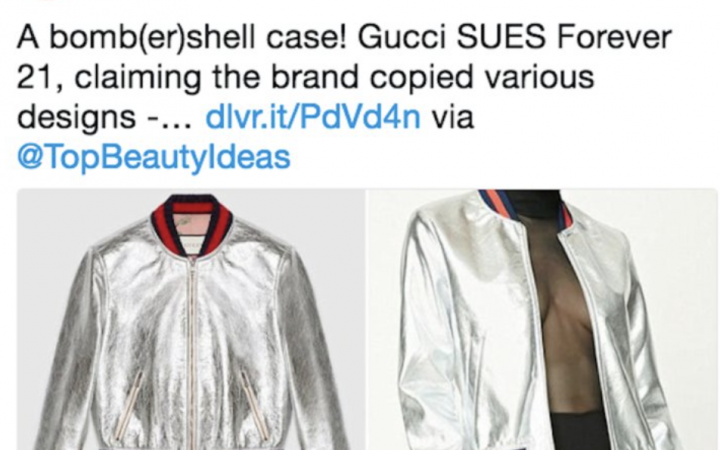 """Screenshot of tweet which reads """"bomb(er) shell case! Gucci SUES Forever21, claiming the brand copied various designs..."""". The picture on the left is the Gucci silver bomber with red and blue stripes on collar, picture on the right shows Forever 21's almost exact copy of the bomber jacket."""