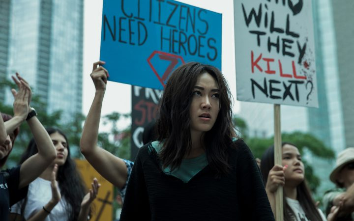 Screencapture from the TV show The Boys. Karen Fukuhara's character stands in the middle of a rally supporting superheroes.