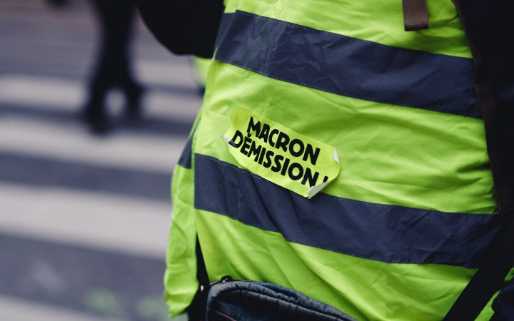 a yellow vest protestor with the words 'Macron Quit' in French