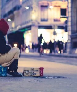 A homeless person sits on a city street corner