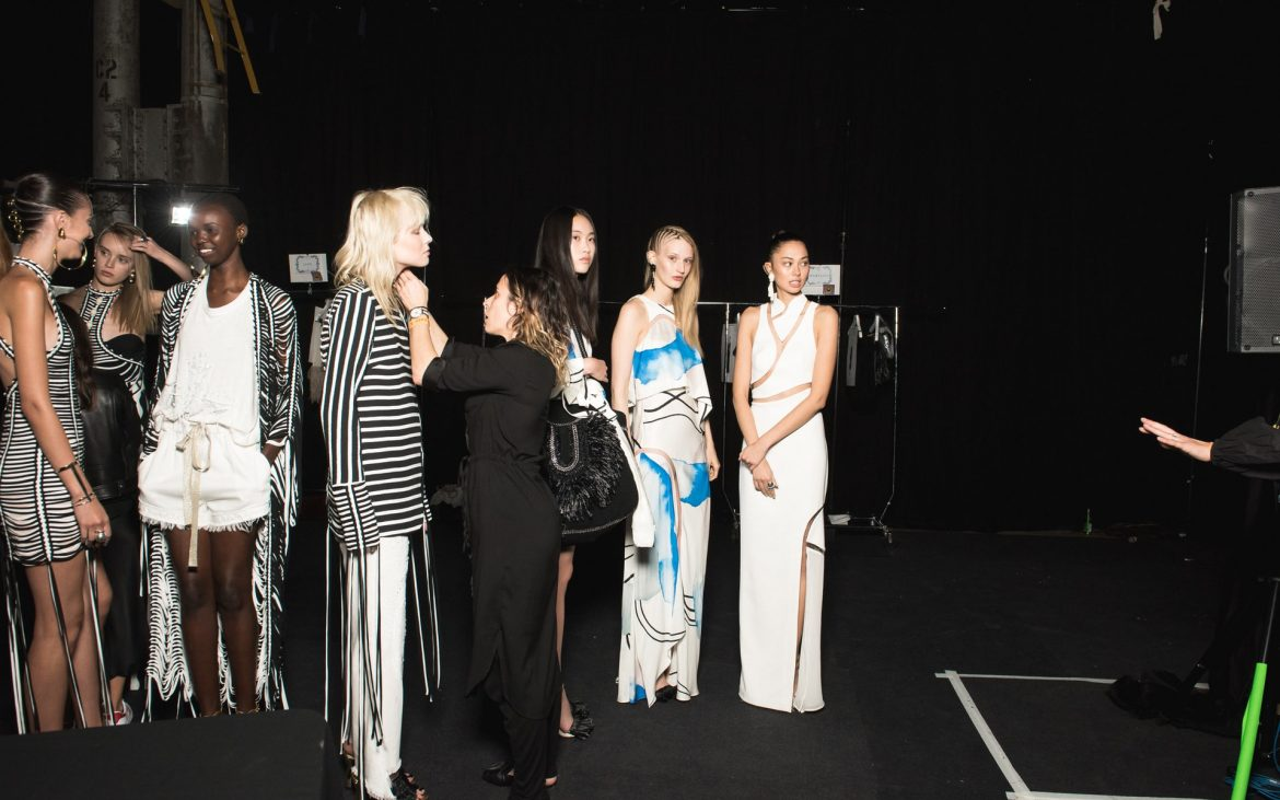 Models standing backstage, designer doing final touch ups to the clothes before fashion show. Black background.