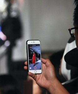 Man recording a runway show during Fashion Week on his smart phone.