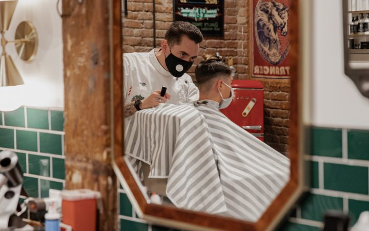 Barber wearing face mask whilst cutting hair