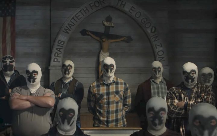 Still from HBO's Watchmen. A group of white supremacists in white masks standing in front of a church. The masks have a rorschach print on them.