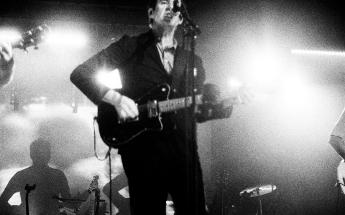 Black & white photo. It is of a white man with black hair and wearing a dark colour suit playing a guitar.