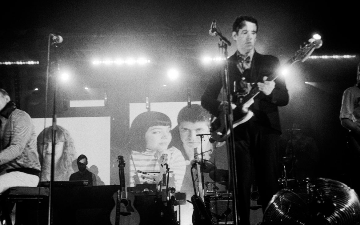 Black & White photo. On the left is a white man playing a piano. The background is a collection of photos of people and amps & guitars. On the right is a white man with dark hair & wearing a dark suit playing a guitar