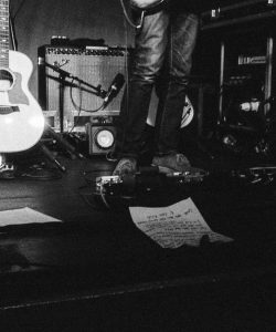 Black & white photo of a stage. There is sereval amps in the background as well as a guitar on the left. On the right is a pair of legs wearing jeans.
