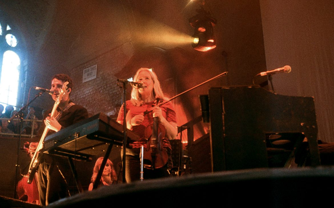 A colour photo with orange hues. On the left is a white man with black hair and wearing a black suit. In the centre is a white women with shoulder length blonde hair wearing a red t-shirt. she is holding a violin. In front of her is a mic and keyboard. On the right is a piano. they are on a stage