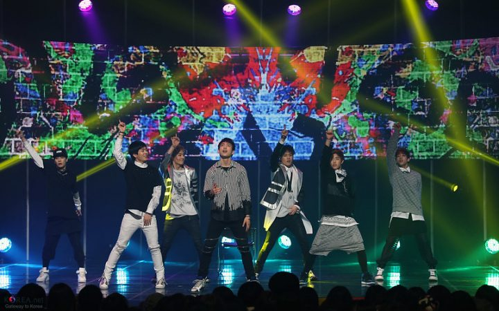 GOT7, performing a show. There are seven members, all male, dancing on a colourful stage with bright lights.