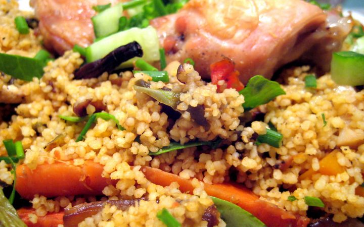 A chicken and couscous dish with added vegetables like basil, carrot, cucumbers, red onion and chopped asparagus