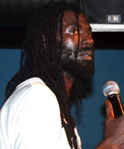 Side profile of Jamaican dancehall artist Buju Banton, wearing a white shirt and holding a microphone. There is a blue wall and a man wearing a black shirt behind him.