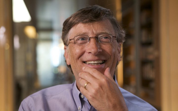 Bill Gates smiling with hand on chin