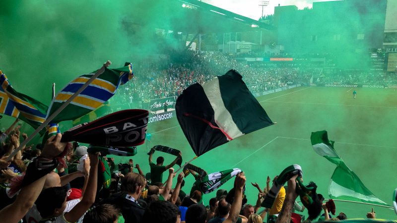 Portland Timbers fans displaying Cascadia imagery amongst a cloud of green smoke