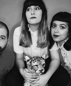 the photo is black & white. There is three people. On the left is a white man wearing a shirt with a shaved head & a beard. In the centre is a young white women with long dark hair with a fringe. She is holding a toy leopard. On the right is another young white women with dark hair with a fringe wearing a white blouse, & heavy eyeliner. The background is a plain gray.