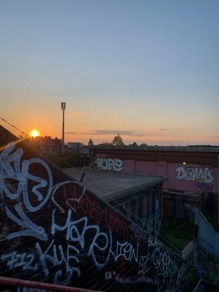 Various tags cover a wall in the foreground, 'throw up' spelling out 'VOPE' is in the distance whilst the sun sets in the background.
