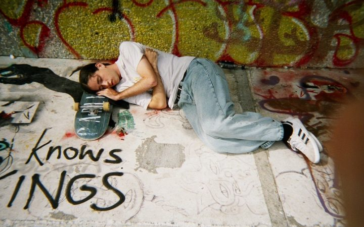 Image of Blake sleeping on his sleepboard at a skatepark in Berlin