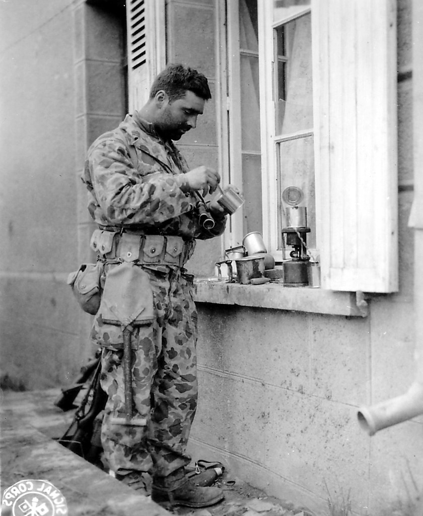 """Soilder wearing camouflage clothing opening a tin can, standing near an open window, image is in B&W. from Creative Commons - (""""p013379"""" by PhotosNormandie) is licensed under CC BY-SA 2.0"""