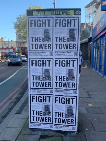 Telephone box covered with posters stating 'fight the tower'