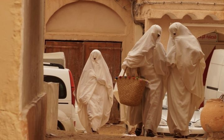 Walking on the side street three women are wearing a white burqa which is a white cloth that covers them from head to toe and exposes a single eye