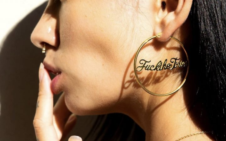 "A woman's side profile, wearing a gold hoop earring which says ""Fuck the Tories"" in cursive handwriting."