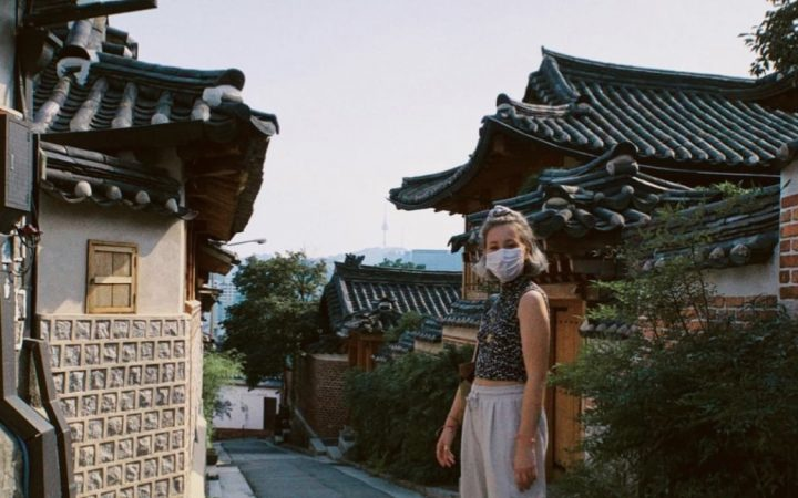 A girl wearing a blue top and beige trousers, standing in Bukchon Hanok Village, a traditional Korean housing area in Seoul, South Korea