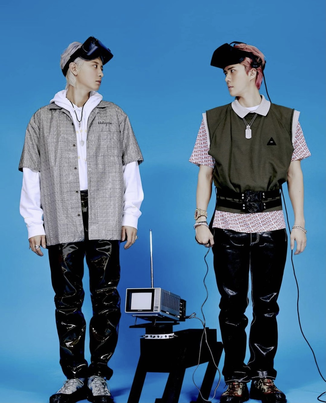 Park Chanyeol and Oh Sehun, wearing VR headsets in front of a blue backdrop, facing the camera but looking towards each other.