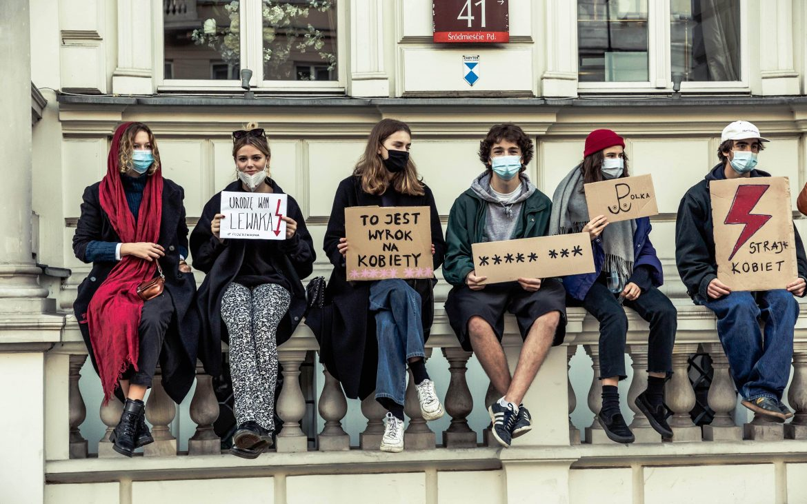 Young polish protestors sit on building with placards against abortion ruling