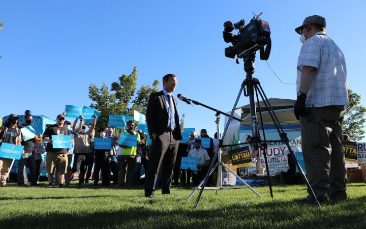 Libertarian candidate Spike Cohen stands in front of a group of supporters while doing an interview at a rally in Utah