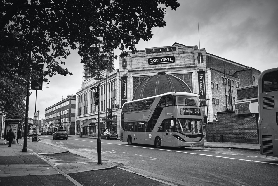 Grayscale image of double decker bus driving past Brixton Academy