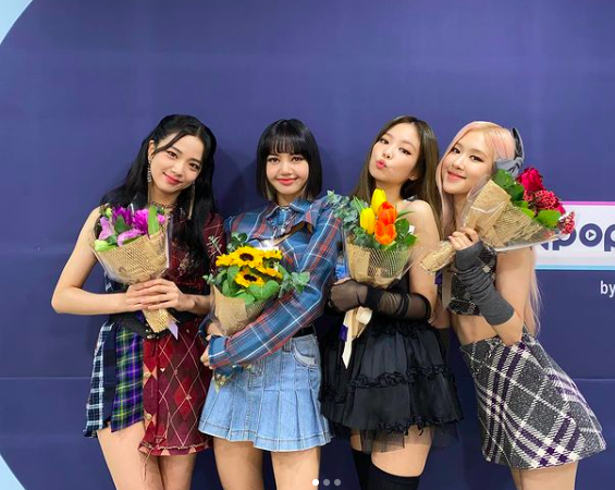 (Left to right) Jisoo, Lisa, Jennie and Rosé of KPop girl group Blackpink, holding bunches of flowers.