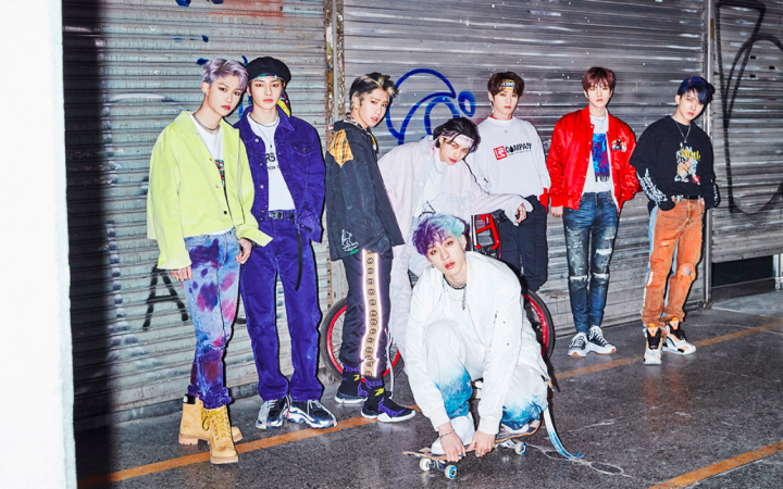 8 boys, known as Stray Kids, wearing colourful outfits on the set of the God's Menu music video.