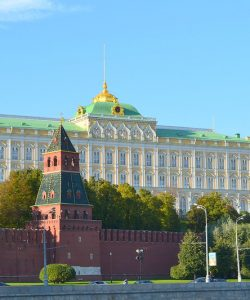 A view of the Kremlin, behind a red wall and in front of a blue sky.