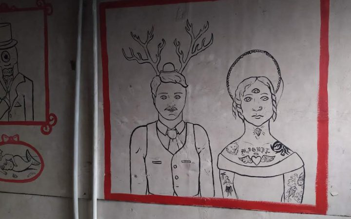 Art in the shower room of a man with antlers and a woman with a hat with a red border.