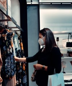 Woman in clothes shop in wearing face mask