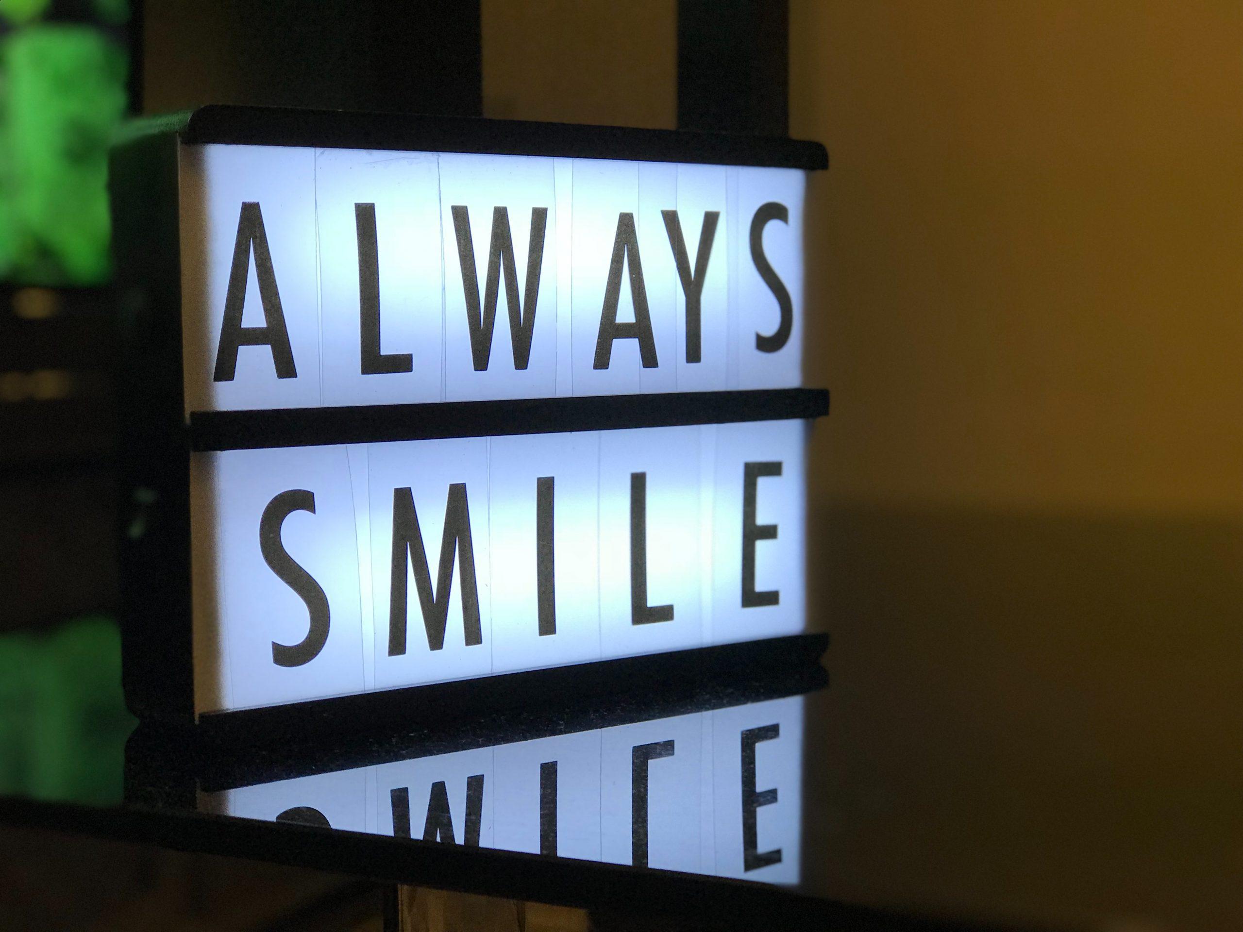 Illuminated sign saying 'Always Smile'