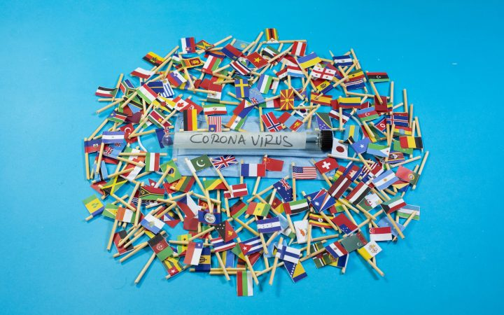 All countries flag with Corona Virus test tube and surgical mask. Photo by GR Stocks on Unsplash.